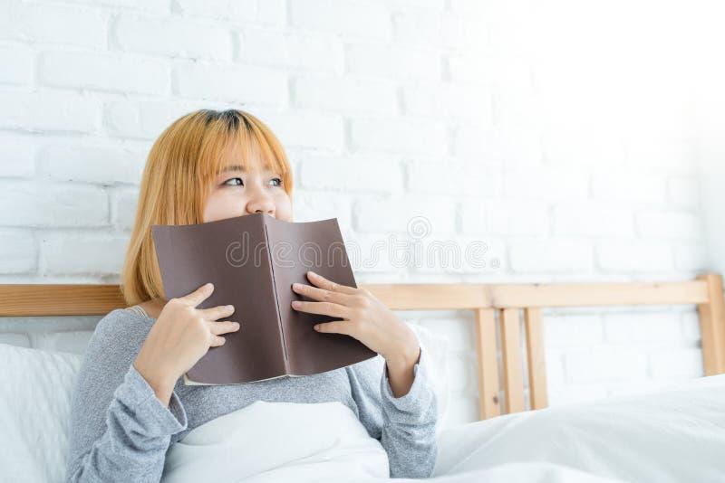 Lycklig ung asiatisk kvinna för livsstil som tycker om att ligga på sängläseboknöjet i tillfälliga kläder hemma royaltyfri fotografi