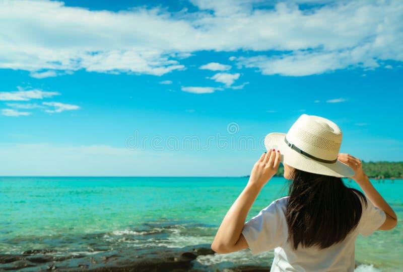 Lycklig ung asiatisk kvinna i mode för tillfällig stil med ställningen för sugrörhatt på havsstranden av semesterorten i sommarse arkivbilder