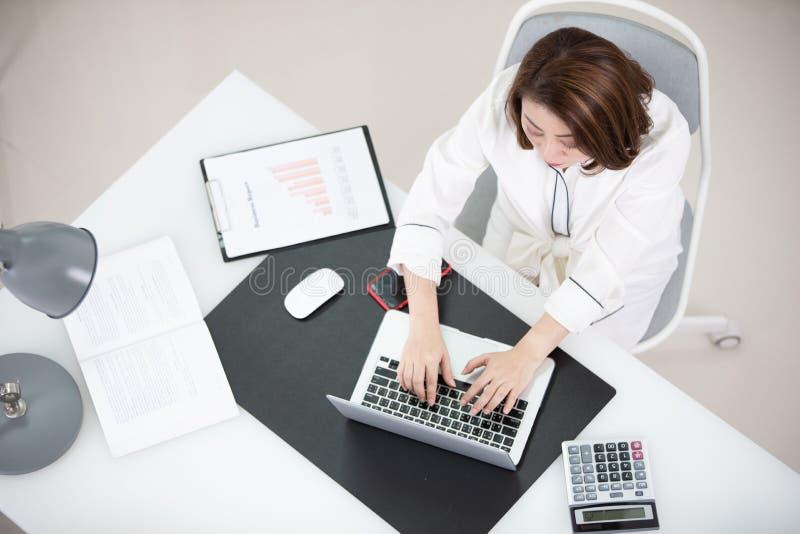 Lycklig ung asiatisk kvinna på kontoret arkivfoton