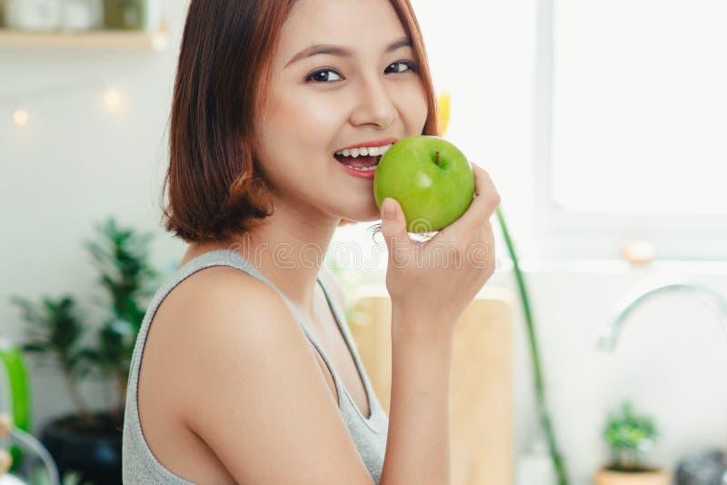 Lycklig ung asiatisk kvinna som äter gröna Apple på kök banta matris royaltyfri foto