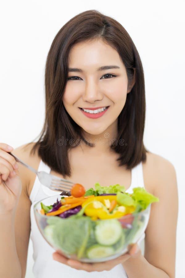 Lycklig ung asiatisk kvinna som äter sund sallad som isoleras på vit w royaltyfri fotografi
