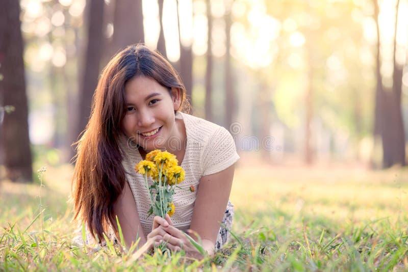 Lycklig ung asiatisk kvinnainnehavblomma och ligga ner på gräs royaltyfri fotografi
