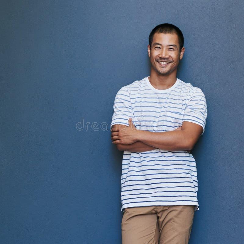 Lycklig ung asiatisk man med avkopplad inställning royaltyfri bild