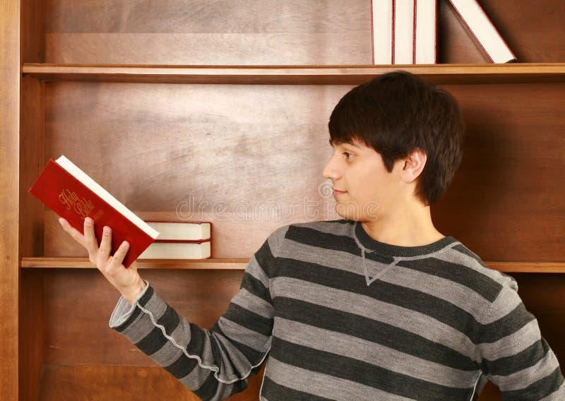 Lycklig ung asiatisk man med bibeln arkivfoto