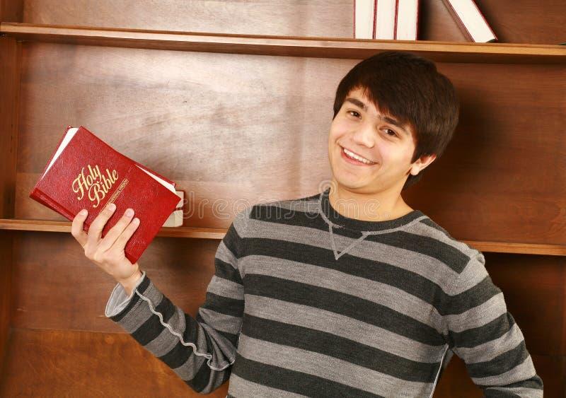 Lycklig ung asiatisk man med bibeln arkivbild