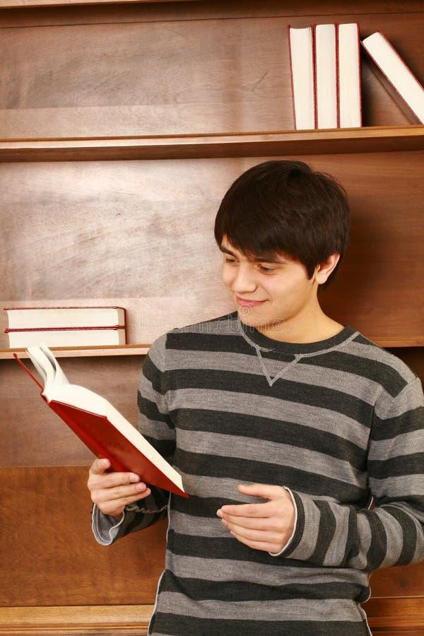 Lycklig ung asiatisk man med boken arkivfoton
