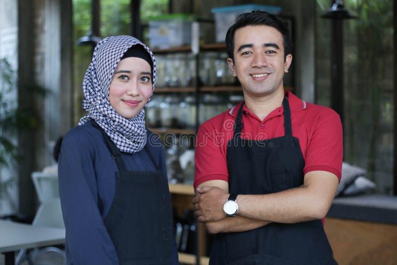 Lycklig ung asiatisk parkaféägare framme av att le för coffee shop stående av två uppassare på restaurangen arkivfoton
