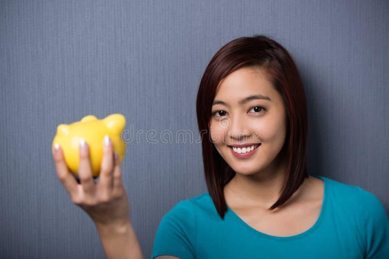 Lycklig ung asiatisk student som rymmer en spargris royaltyfria bilder