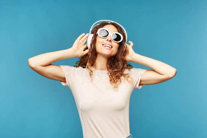Lycklig ung bekymmerslös kvinnlig i hörlurar som tycker om musik arkivbilder