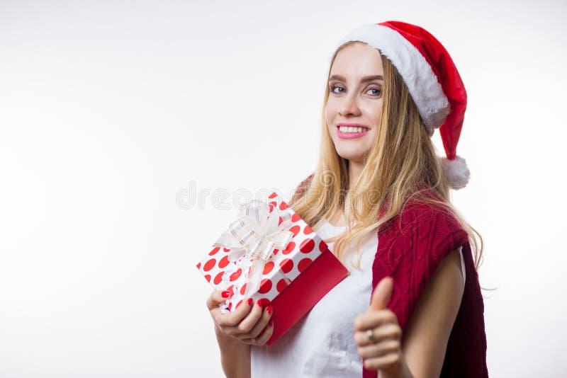 Lycklig ung blond kvinna som rymmer en gåvaask på hennes hand och visar tummen upp på vit bakgrund Nytt år sinnesrörelser, jul, royaltyfri foto