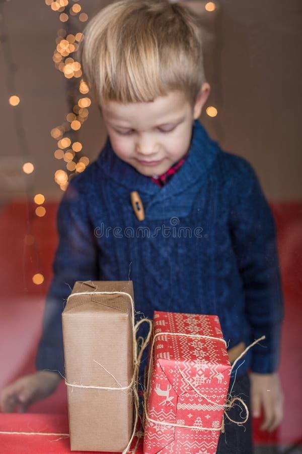 Lycklig ung blond pojke med gåvaasken Jul Födelsedag arkivfoto