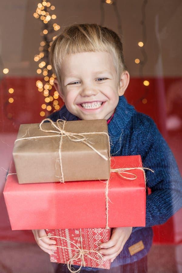 Lycklig ung blond pojke med gåvaasken Jul Födelsedag arkivbild