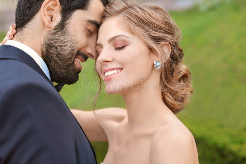 Lycklig ung brud med hennes brudgum utomhus royaltyfri fotografi