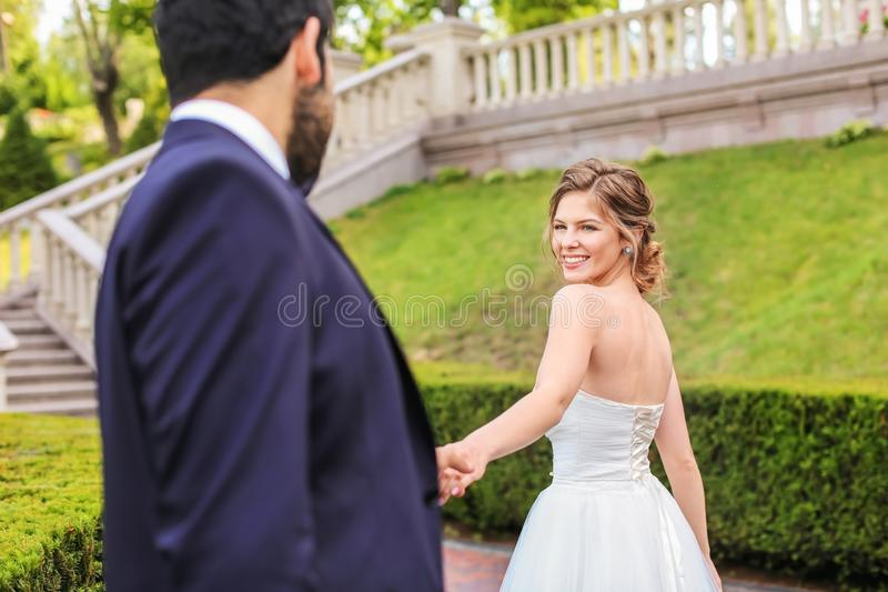 Lycklig ung brud med hennes brudgum utomhus arkivbild
