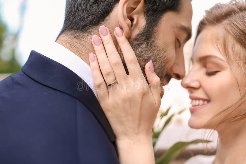Lycklig ung brud med hennes brudgum utomhus, closeup royaltyfri foto