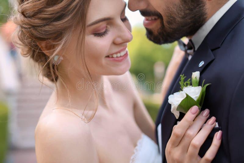 Lycklig ung brud som fäster knapphålet till hennes brudgums omslag royaltyfri foto