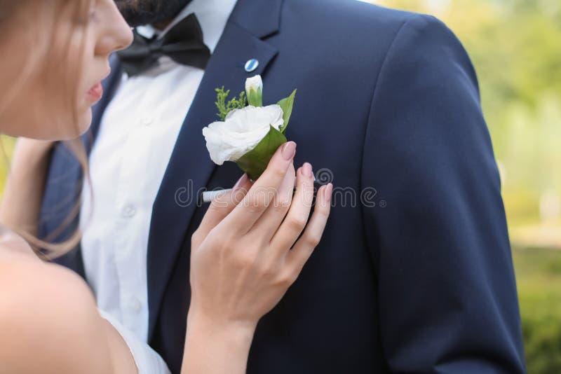 Lycklig ung brud som fäster knapphålet till hennes brudgums omslag, closeup arkivbild