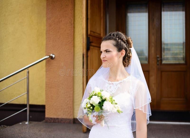 Lycklig ung brud som framme står av kyrkan arkivfoton