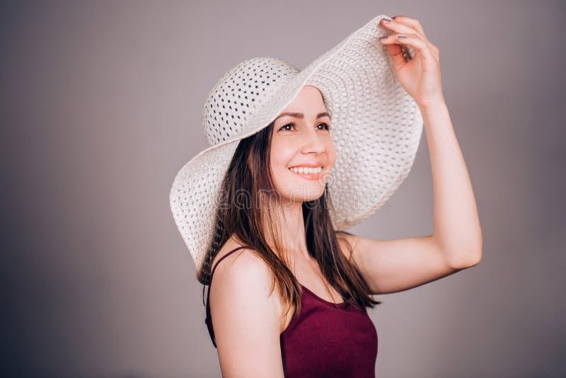 Lycklig ung brunettkvinna i beige hatt med glädje och leendet som bort ser fotografering för bildbyråer