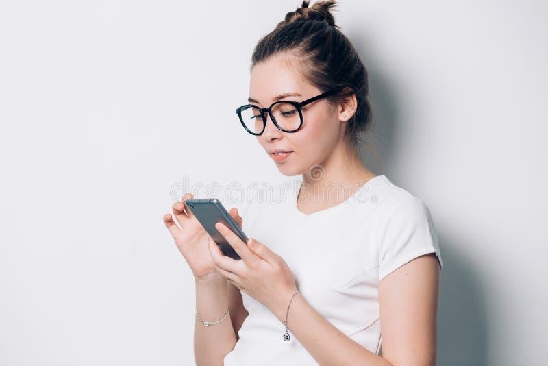 Lycklig ung brunettkvinna som ler och använder smartphonen på vit bakgrund Modern teknologi, internet, kommunikationsmeddelande arkivbild