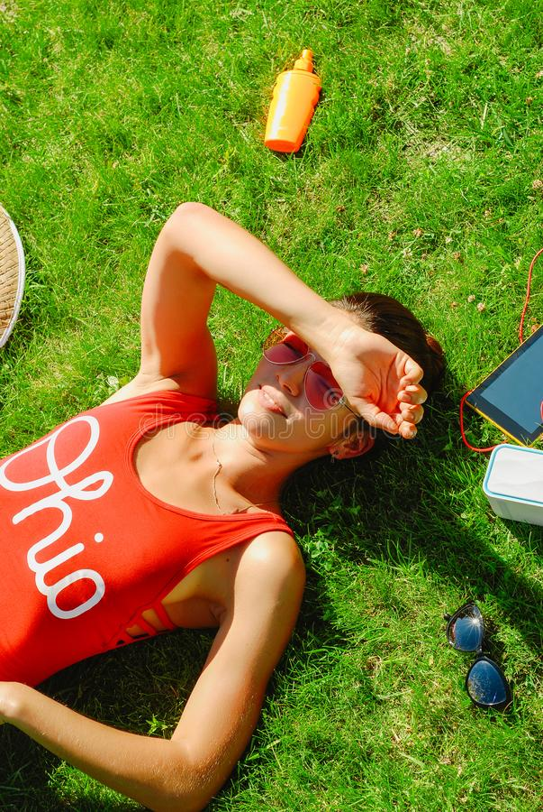 lycklig ung brunettkvinna som lyssnar till musiken som är utomhus- på en sommardag arkivbild