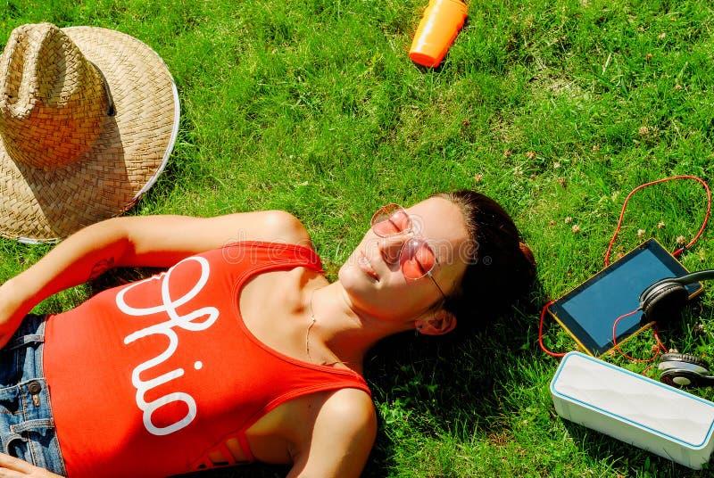 lycklig ung brunettkvinna som lyssnar till musiken som är utomhus- på en sommardag royaltyfri foto