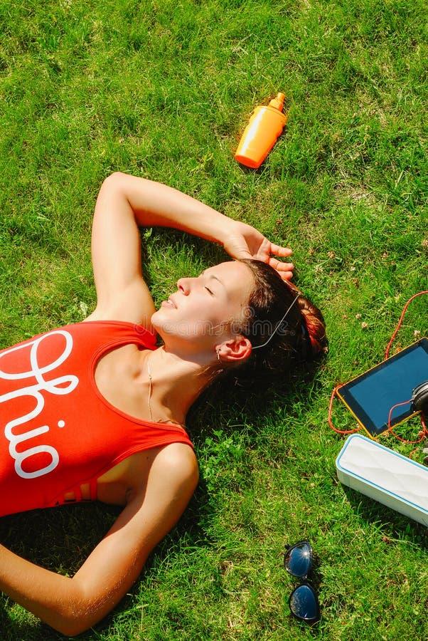 lycklig ung brunettkvinna som lyssnar till musiken som är utomhus- på en sommardag royaltyfri bild