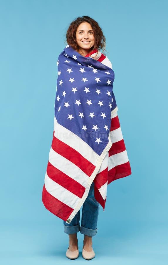 Lycklig ung brunettkvinnlig som slås in in i amerikanska flaggan royaltyfria bilder
