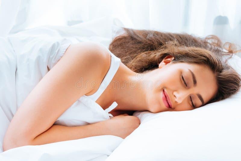 Lycklig ung Caucasian kvinna som ler och sover i säng med avkoppling och stillsam och lugna mening i vit bakgrund royaltyfria bilder
