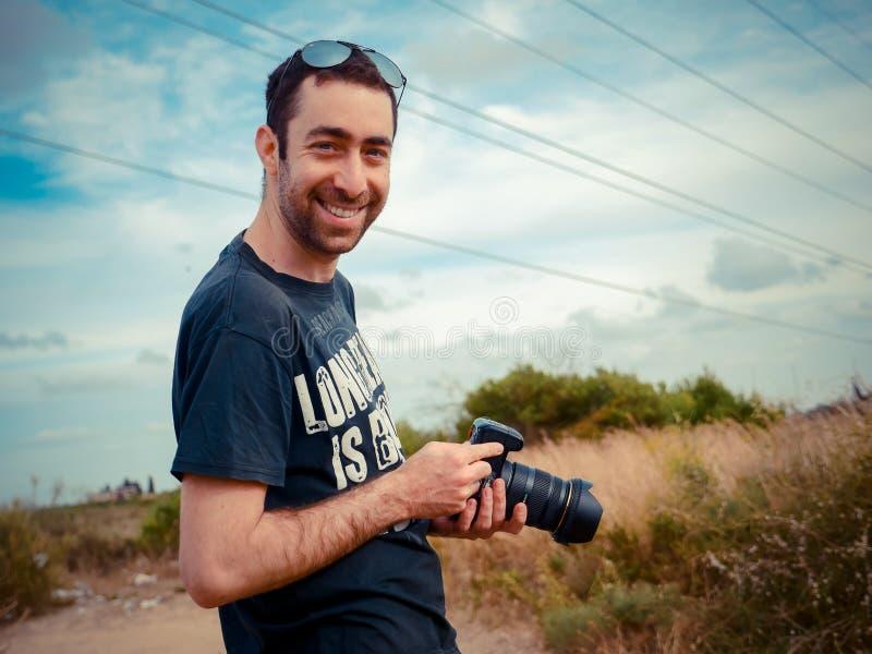 Lycklig ung caucasian manfotograf som rymmer en digital kamera i hans hand och ler till kameran som är utomhus- i fältet arkivfoto