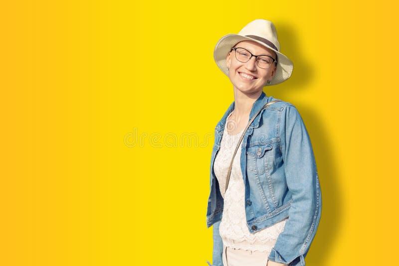 Lycklig ung caucasian skallig kvinna i hatt och tillf?llig kl?der som tycker om liv, n?r att ha fortlevt br?stcancer h?rlig st?en royaltyfri fotografi