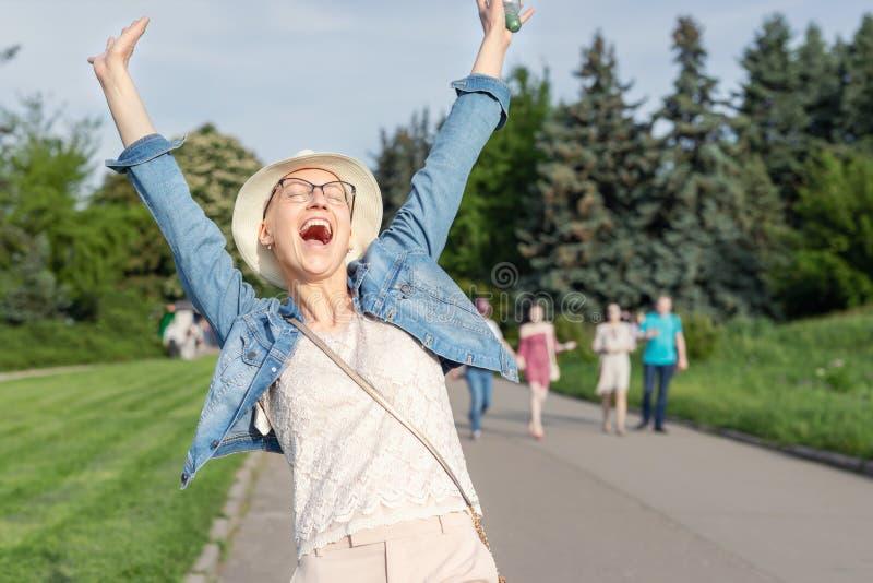 Lycklig ung caucasian skallig kvinna i hatt och tillf?llig kl?der som tycker om liv, n?r att ha fortlevt br?stcancer h?rlig st?en arkivbild