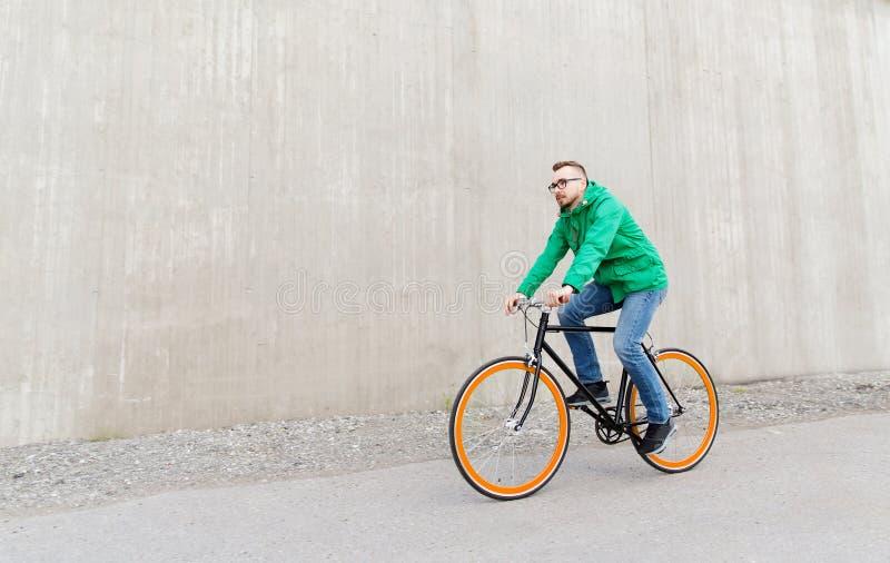Lycklig ung cykel för kugghjul för hipsterman ridning fixad royaltyfri bild