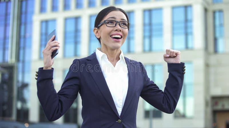 Lycklig ung dam som visar framgångtecknet som mottar jobberbjudande, lyckad start royaltyfria bilder