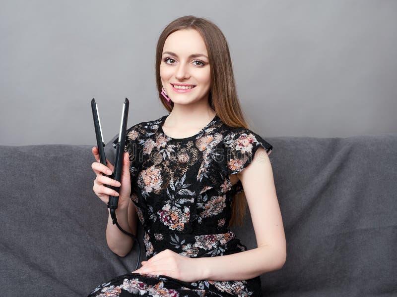 Lycklig ung förtjusande kvinna i lång klänning på hållande hårstyler för grå soffa upp hemma mot den gråa väggen fotografering för bildbyråer