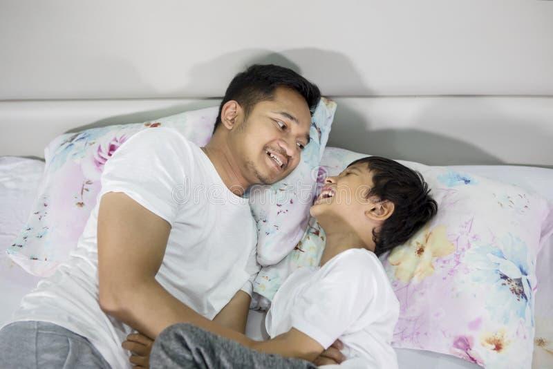 Lycklig ung fader som killar hans son på sängen arkivfoto