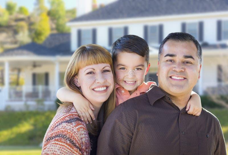 Lycklig ung familj för blandat lopp framme av huset royaltyfria foton