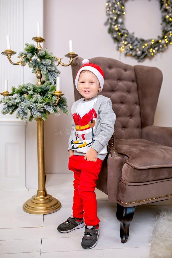 Lycklig ung familj, fader, moder och son, i julafton i hem Lite pojke i jultomten hattställning nära fåtöljen och arkivfoto