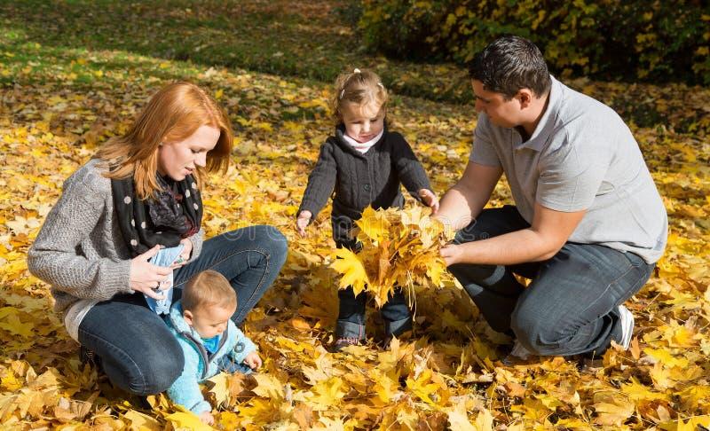 Lycklig ung familj i hösten som gör en gå och en lek med lönn l royaltyfria foton