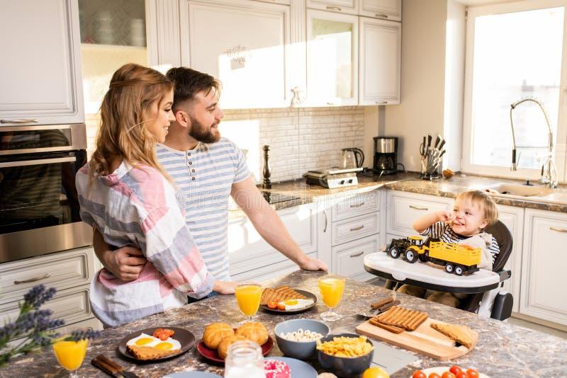 Lycklig ung familj i kök arkivbilder