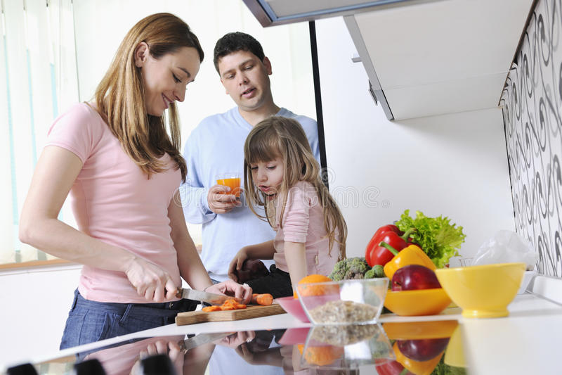 Lycklig ung familj i kök royaltyfri fotografi