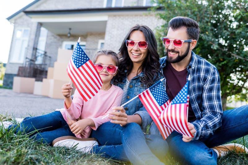 lycklig ung familj med amerikanska flaggan och solglasögon som sitter i trädgård av arkivbilder
