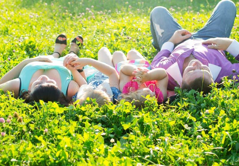 Lycklig ung familj med barn som ligger på gräset i sunshen arkivbilder