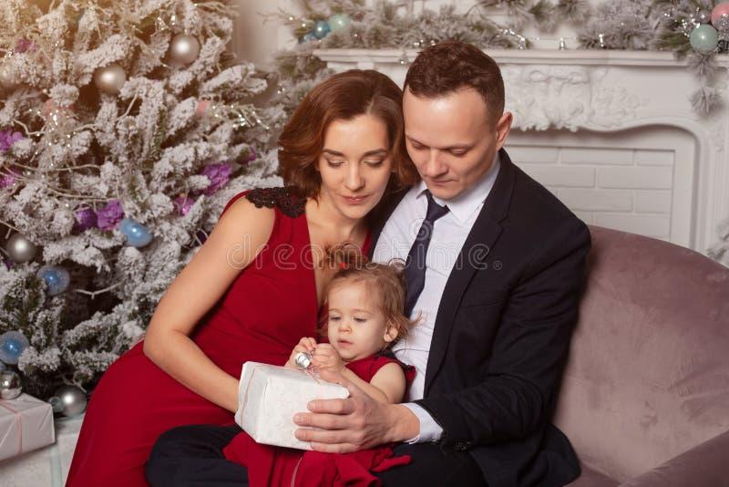 Lycklig ung familj med en hållande julgåva för barn Sitta på soffan nära julgranen hemma fotografering för bildbyråer