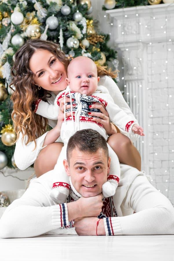 Lycklig ung familj med sonen nära jul arkivfoto