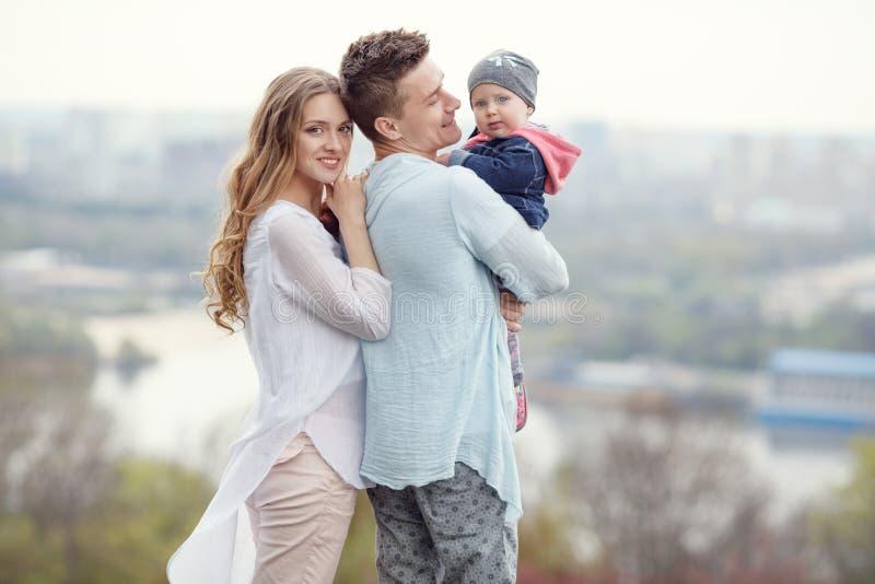 Lycklig ung familj på stadsbakgrunden fotografering för bildbyråer