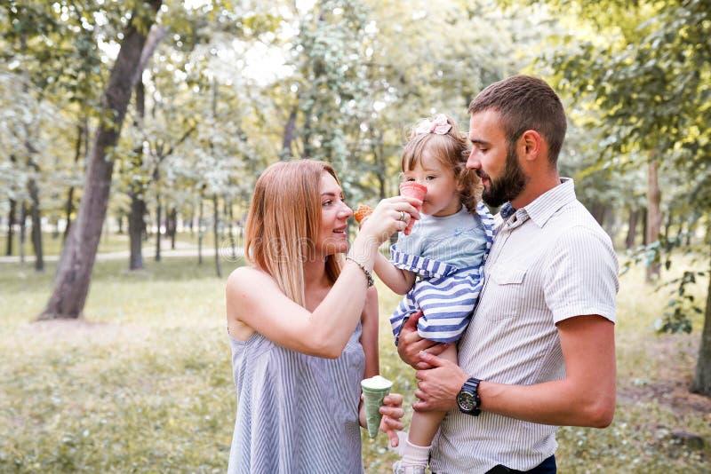 Lycklig ung familj som äter glass och har den roliga yttersidan arkivbilder