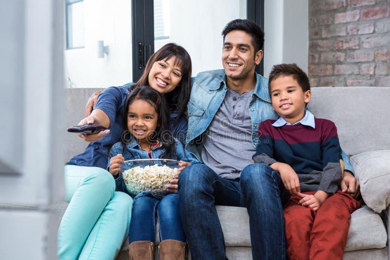 Lycklig ung familj som äter popcorn, medan hålla ögonen på tv royaltyfri bild