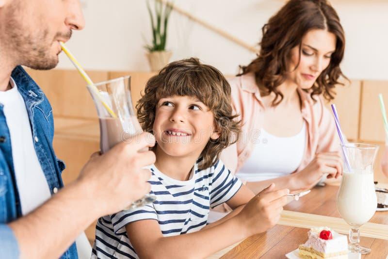lycklig ung familj som dricker milkshakar, i kafé och att spendera royaltyfri foto
