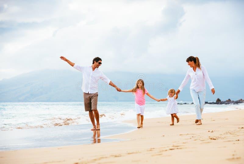 Lycklig ung familj som går på stranden royaltyfria bilder